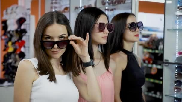 Mladé dívky kupují sluneční brýle v malém butiku.