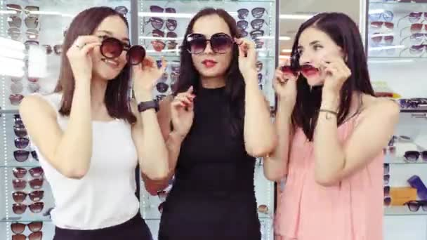 The company of girls comically demonstrate sunglasses. Stop motion.