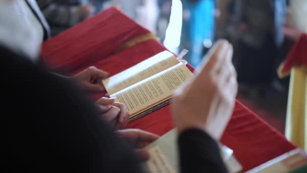Kirchenchor. Nahaufnahme der singenden Chorleiter vor dem Hintergrund des Buches.