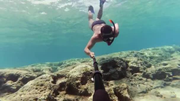 Junger Mann taucht ein, um Statue auf dem Meeresgrund zu beobachten