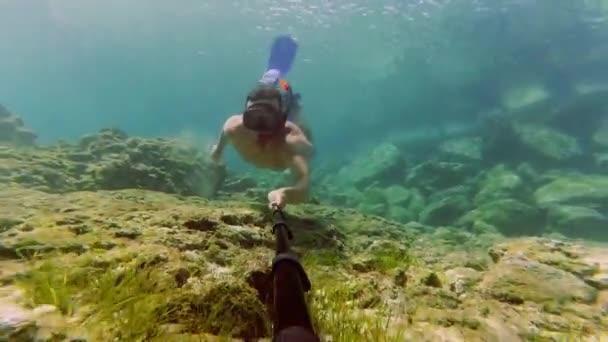 junger Mann taucht mit Schnorchel und dreht Unterwasser-Video von sich mit seiner Action-Kamera
