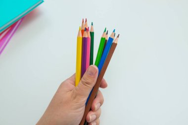 Female hand holding a set of colored pencils on light gray background with notebooks, copy space. Drawing and education theme.