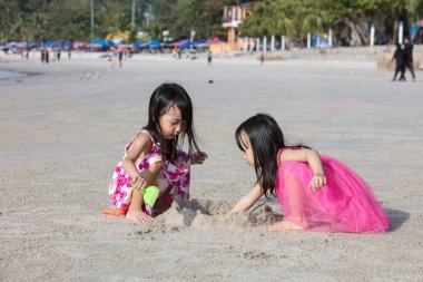 Asian Chinese little sisters playing sand at beach outdoor