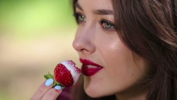hübsche Frau isst verführerisch Erdbeeren