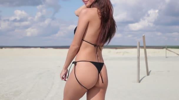 Kacér nő, fekete bikini séta a homokos strandon