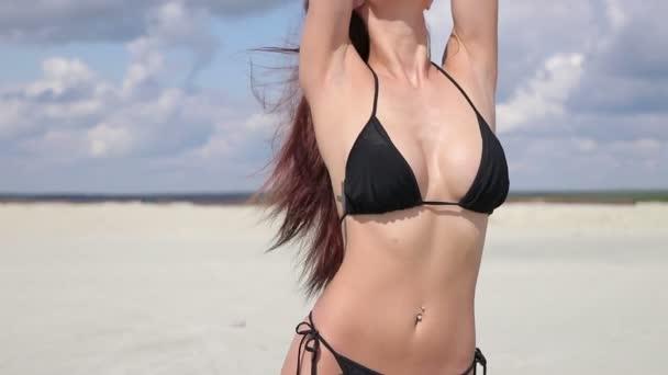 Érzéki nő fekete bikini álló és élvezi napsütés