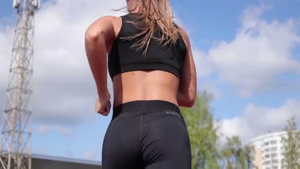 Štíhlá žena, která běží na závodní dráze na slunci