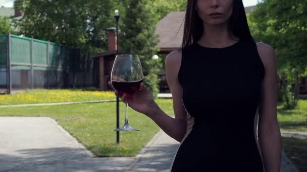 Elegáns nő üveg borral sétál a kastély kertjében