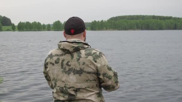Rybář točí rybářským kotoučem. Rybaření na letní řece