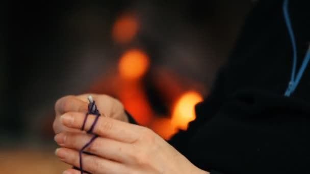 female hands crocheting in front of fireplace, close-up