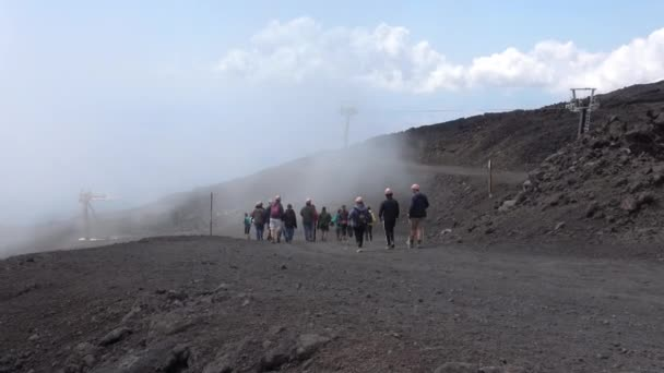 Hikers on a volcanic path of Mount Etna, Etna national park, Sicily, Italy. Smoke and clouds, 4k footage