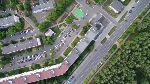 kvadrokopter plující nad městem, střechami a parkovacími partiemi