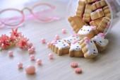 néhány pinky és aranyos hello kitty cookie-k jönnek ki az üveget a fából készült asztal