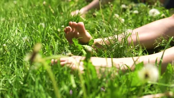 Feet in the grass womens white on a green background move, and sunbathe, happy girls summer outdoors