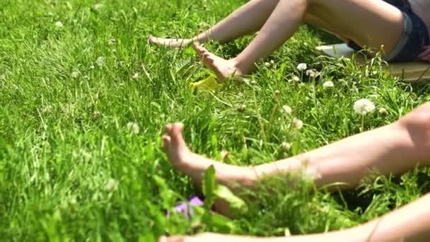 Lábak a fűben nők fehér zöld háttér mozog, és napozás, boldog lányok
