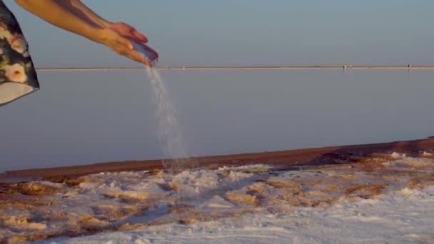 Sysypet Salz aus den Händen eines Mädchens in einem Kleid vor dem Hintergrund des Sees