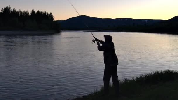 Rybář v noci rybaří s otočnou tyčí na pozadí hor v řece