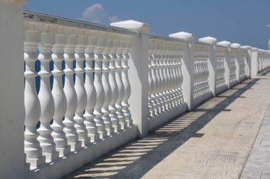 Baluster beach. White columns overlooking the sea. View of white pillars and horizont on blue sea and the sky in the background