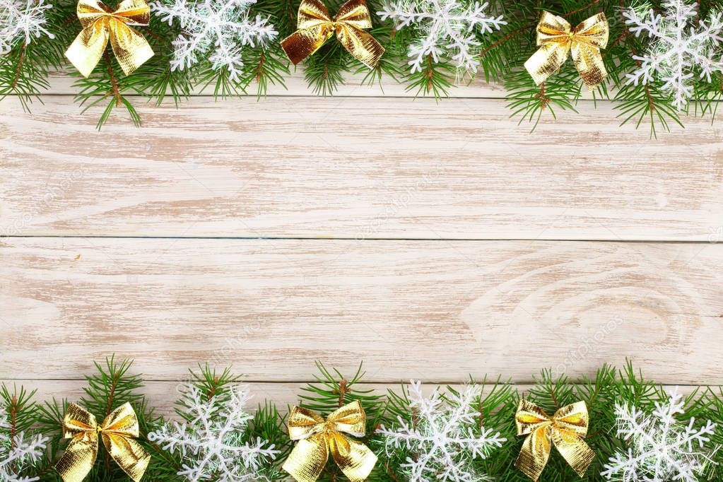 Christmas frame made of fir branches decorated with snowflakes and gold bows on a light wooden background