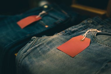 Red tag on jeans for New arrival clothes or sale and discount label template mockup.