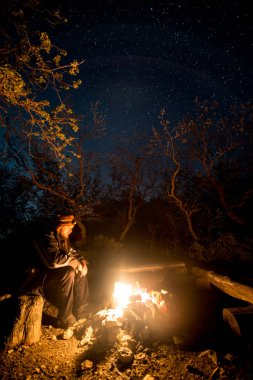Man near the burning bonfire in the night under a starry sky