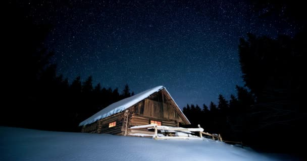 Time-lapse. Beautiful wooden house in the winter forest under the stars