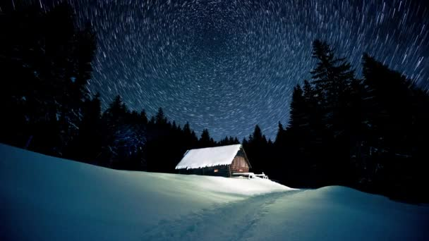 Time-lapse. Star circles over wooden house in the winter forest