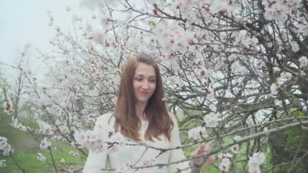 Beautiful girl near blossoming tree in spring
