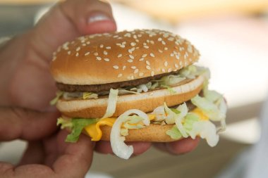 hamburger with beef Patty and salad in a man's hand. Concept of harmful nutrition