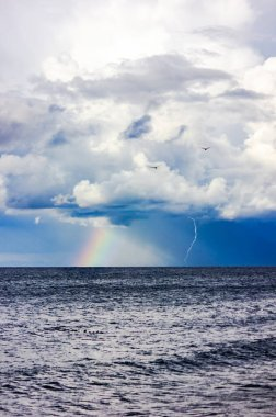 Russia, Kaliningrad region, rainbow and lightning after a storm in the Baltic Sea. Thunderclouds and the sea