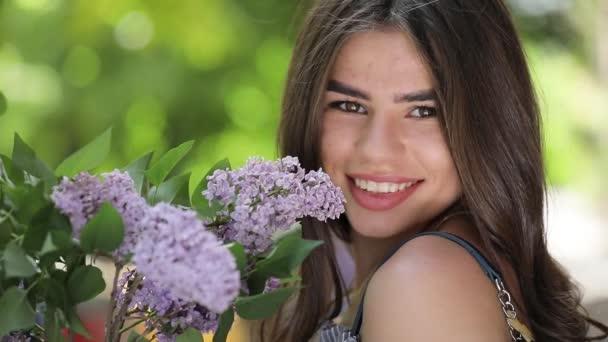 Šťastná žena, usmíval se a užijte si držet fialovými květy kytice