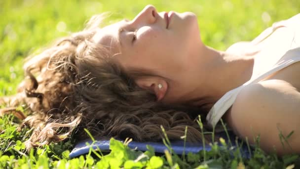 Young woman lying on grass, turn face looking at camera and smile
