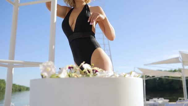 Attractive glamourous fashion model in bikini posing at the beach