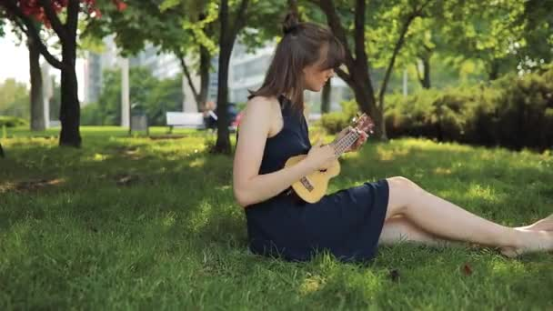 Young woman play on ukulele, little guitar