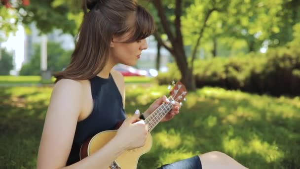 Young woman play on ukulele, little guitar