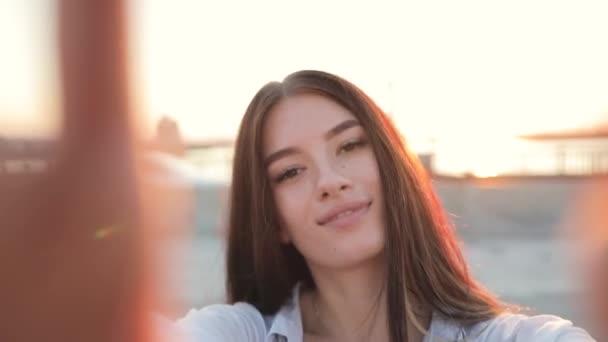 Junge, lächelnde Frau Holding Kamera zeigt Zunge in Sonnenstrahlen, Zeitlupe