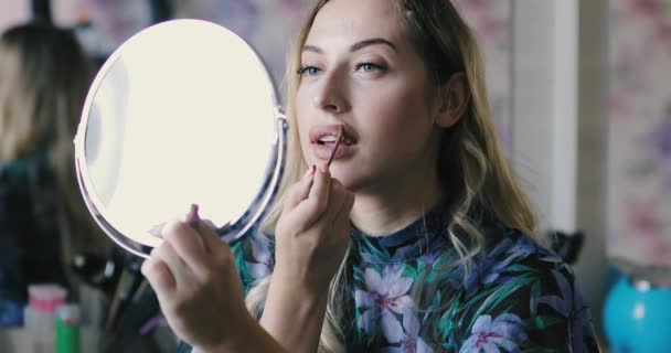 Woman colors her lips, makeup herself