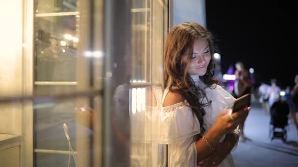Woman browsing smartphone using app in night city