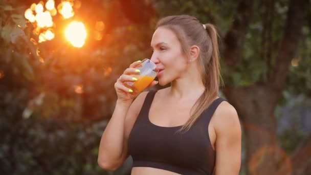 Adult woman drinking orange juice in a garden, healthy lifestyle concept