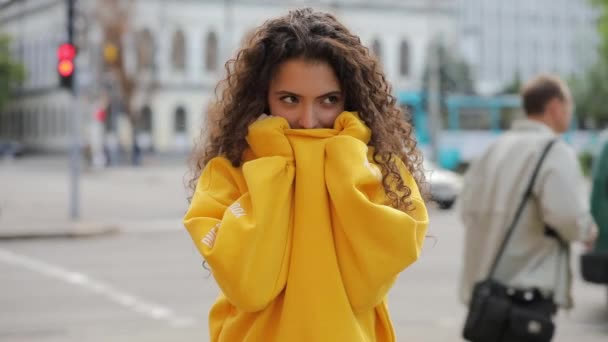 Niedliche lockige Teen Mädchen versteckt unter orange Kleidung
