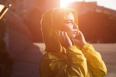 Serious woman under yellow hood with earbuds listening a music at sunny day