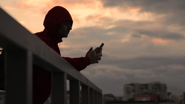 Silhouette of man using smartphone standing on a terrace, cloudy sky evening