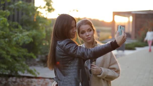 Happy two women friends taking selfie photo resting in resort