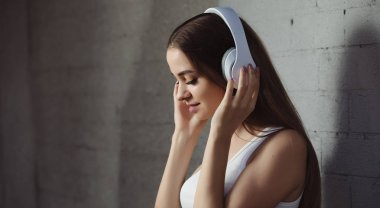 Young woman listening to music with headphones near wall