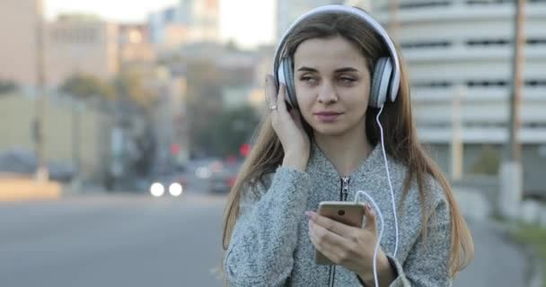 Žena poslechu hudby se sluchátky v městě