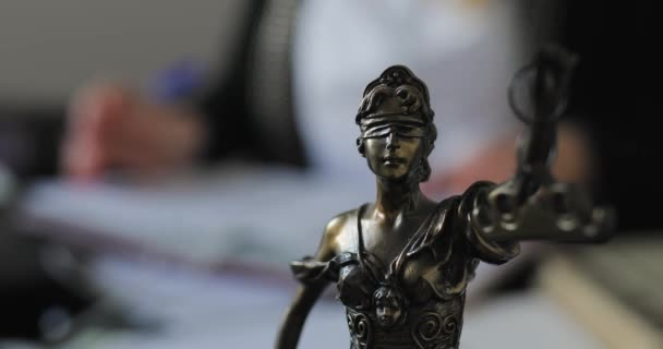 Statuette of Themis on a desk in office, lawyer woman working on background