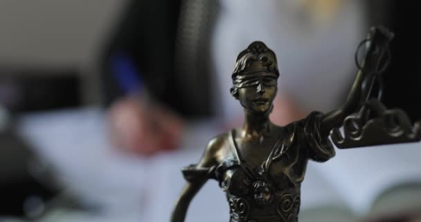 Statuette of Themis on a desk in office, advocate woman working on background