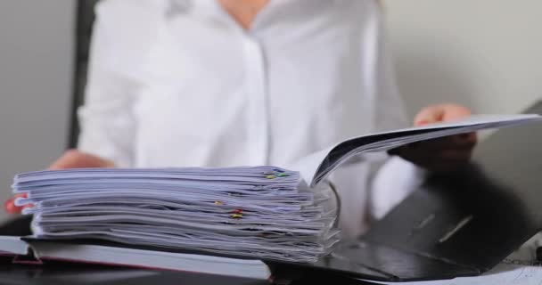 Closeup of woman searching an information in a folder at office