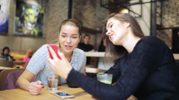 Women friends looking photos in smartphone at cafe