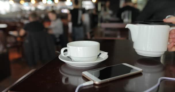 Mužské ruky nalévání čaje do poháru v kavárně